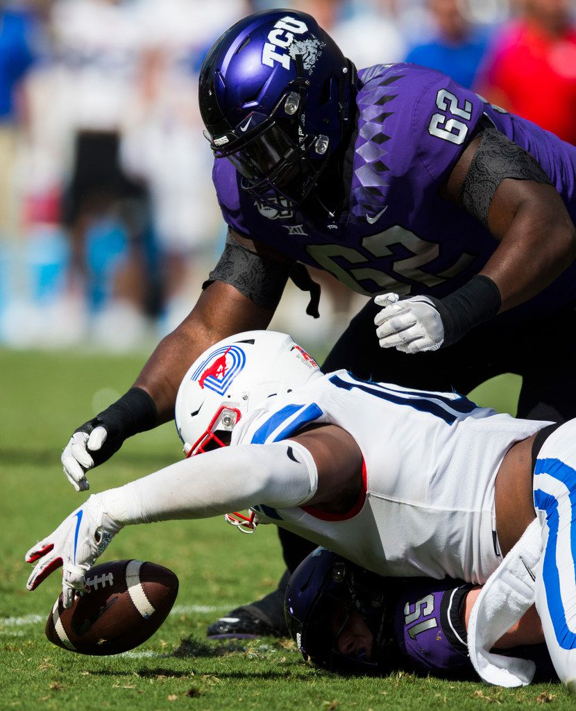 Southern Methodist Mustangs defensive tackle Demerick Gary (10) dives for a gal fumbled by TCU Horned Frogs quarterback Max Duggan (15) during the first quarter of a college football game between SMU and TCU on Saturday, September 21, 2019 at Amon G. Carter Stadium in Fort Worth. TCU Horned Frogs offensive tackle David Bolisomi (62) is at top.