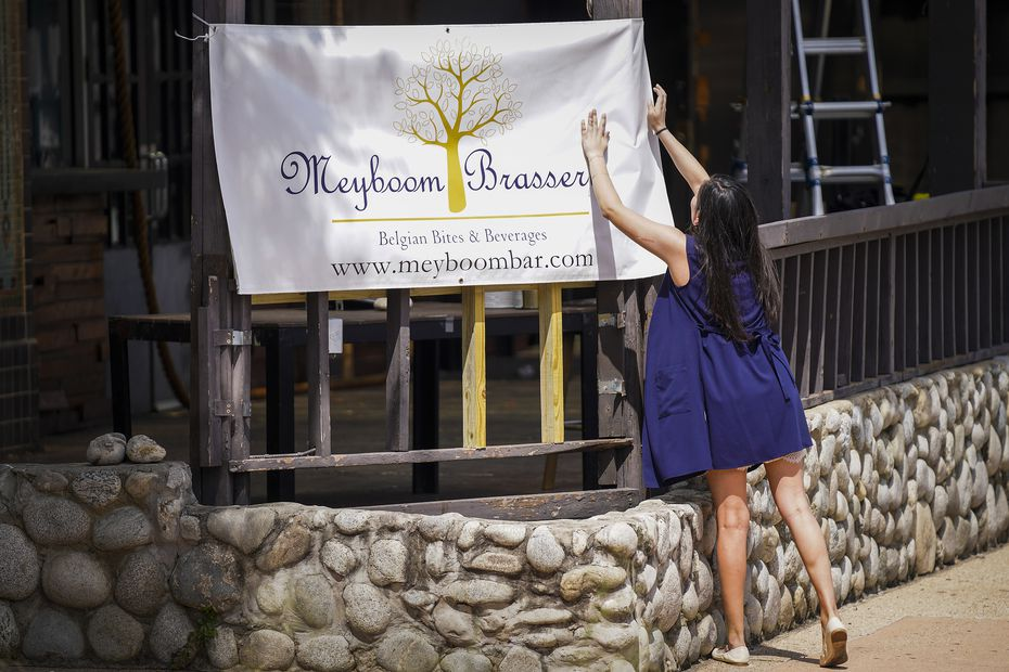 April Segovia hangs a coming-soon banner for her restaurant/bar Meyboom Brasserie at the site of the former Ragin' Crab Cafe on Greenville Avenue in Dallas.
