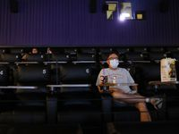 "Dan Dunham of Plano watches trailers play as he waits ""The Invisible Man,"" to start at Cinemark West in Plano, on Friday, June 19, 2020. After being closed for months due to the coronavirus pandemic, the theater reopened in June."