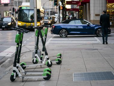 Lime electric scooters sit on the sidewalk on Commerce Street on Wednesday, Dec. 4, 2019 in Dallas.
