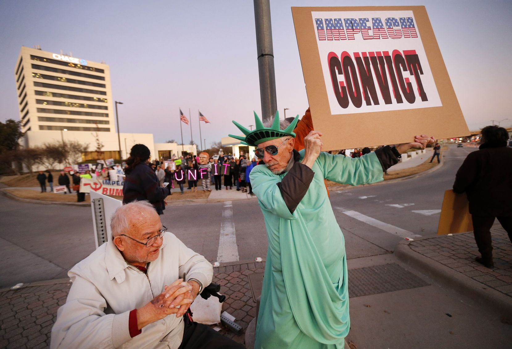 Supporters of U.S. Representative Colin Allred, including Ralph Secketa, 80, (left) and Zen Biasco, gathered outside his Richardson, Texas office at the intersection of Belt Line Rd and Central Expressway to show their support of President Donald Trump's impeachment, Tuesday evening, December 17, 2019.