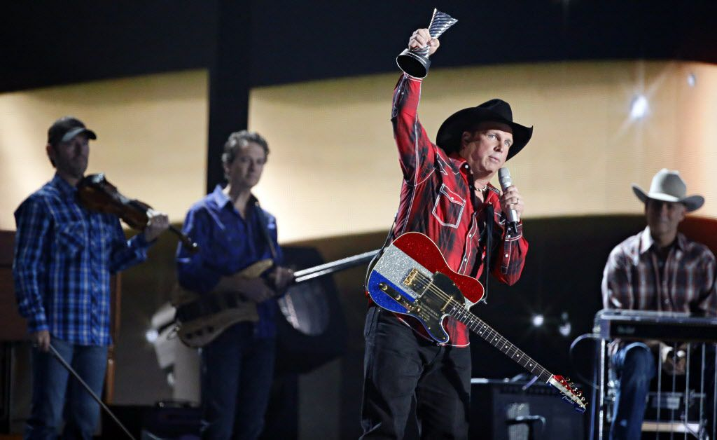 Garth Brooks raises his Milestone Award in the air during the 2015 Academy of Country Music Awards Sunday, April 19, 2015 at AT&T Stadium in Arlington, Texas.