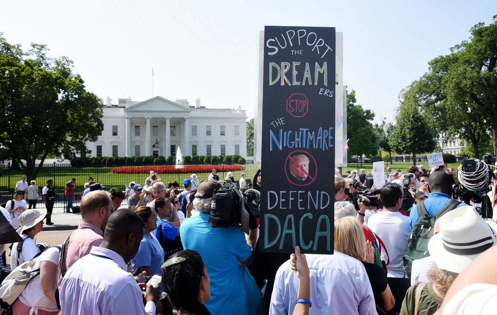 Protesters hold signs during a rally supporting Deferred Action for Childhood Arrivals, or DACA, outside the White House on Sept. 5, 2017.