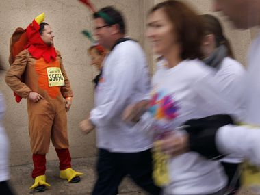 In this 2011 file photo, Thomas Lumpkin, wearing a turkey outfit in the background, waits for his girlfriend at the 44th Capital One Bank Dallas YMCA Turkey Trot, a longtime Thanksgiving tradition. In Irving, the Turkey Trot race will be scaled down this year because of the COVID-19 pandemic.