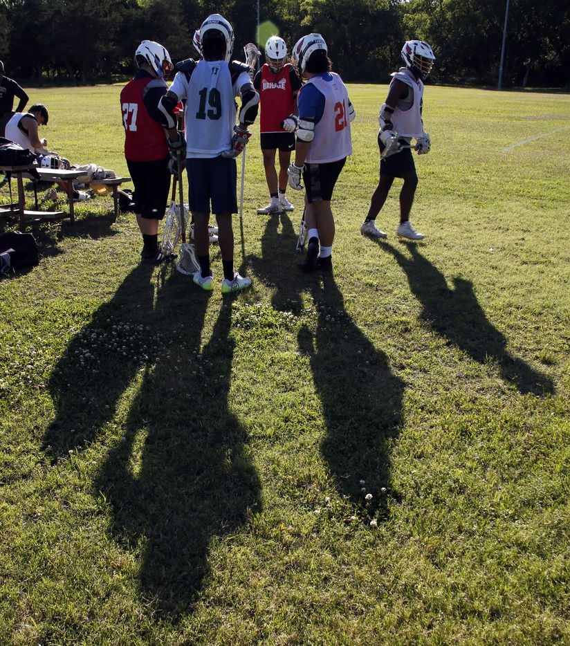 Members of the Bridge Eagles lacrosse team break huddle to start practice with a jog around their practice field. The Bridge lacrosse team held their Wednesday evening practice session at the JC Phelps Recreation Center in Dallas on May 5, 2021.