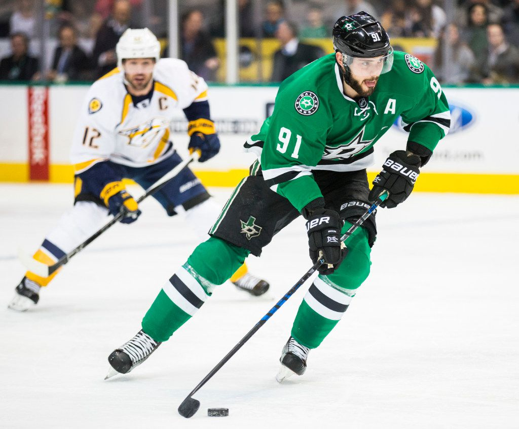 Dallas Stars center Tyler Seguin (91) takes the puck down the ice ahead of Nashville Predators center Mike Fisher (12) during the first period of their game on Thursday, December 8, 2016 at the American Airlines Center in Dallas. (Ashley Landis/The Dallas Morning News)