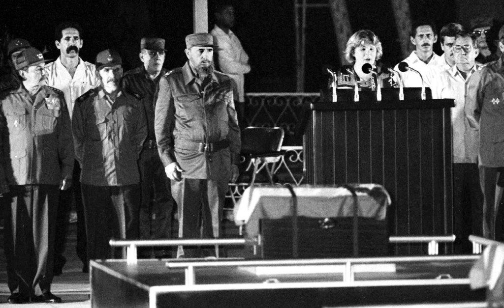"""In this July 12, 1997 photo, Raul Castro, from left, Ramiro Valdes, and Fidel Castro stand as Aleida Guevara, Ernesto """"Che"""" Guevara's daughter, speaks in front of Guevara's remains during a ceremony to pay tribute to the fame guerrilla, in Havana, Cuba."""