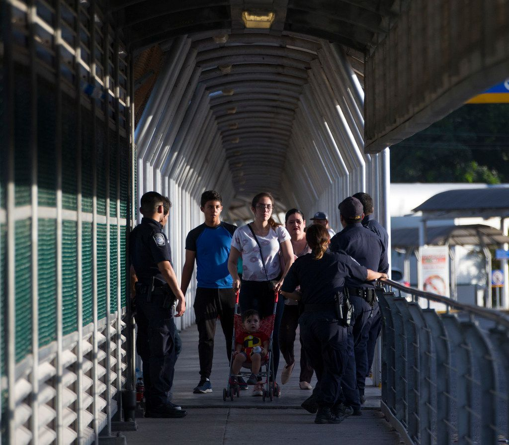 People pass by U.S. Customs and Border Protection officers on the bridge between Hidalgo, Texas, and Reynosa, Mexico, on June 9, 2018.