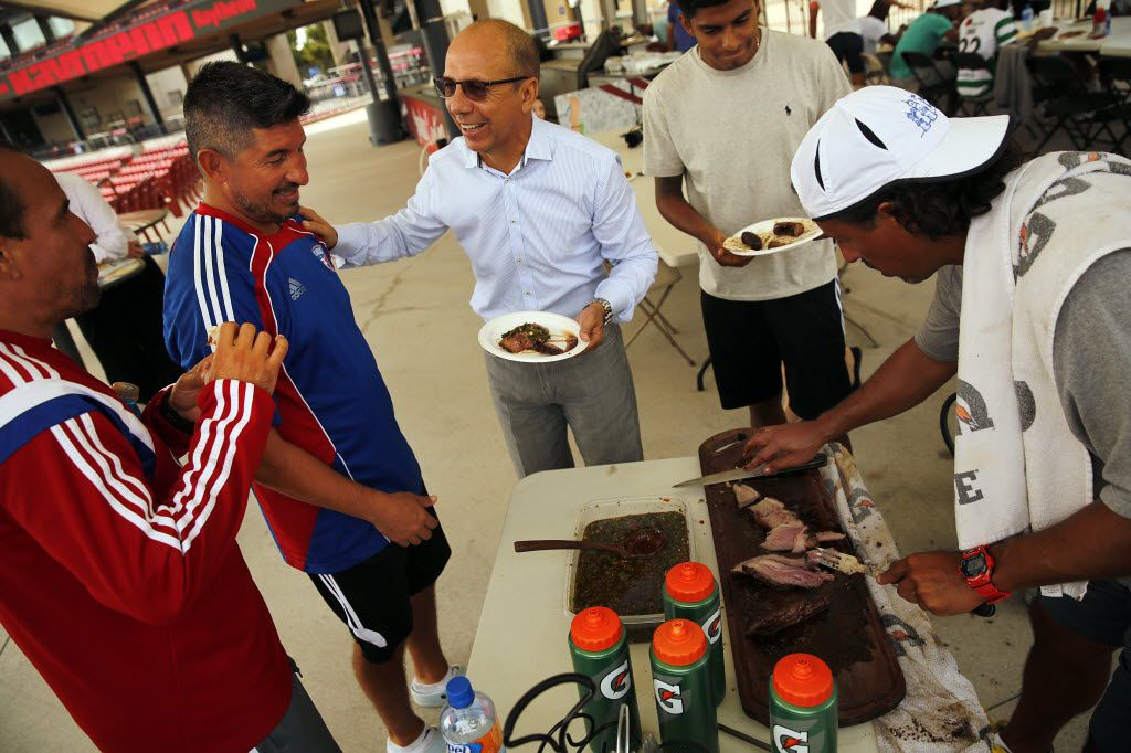 FC Dallas technical director Fernando Clavijo (center) visits with academy coach Victor Medina (blue short) and head coach Oscar Pareja (left) during a cookout for players coaches and staff at Toyota Stadium following practice in Frisco, Texas, Wednesday, October 8, 2014.  Assistant coach Josema Bazan and Pre Academy coach Francisco Molina grilled 50 pounds of Mexican beef fajita Nortena and Picanha Brazilian cut as well as a robust serving of sausage. The cookout has become a weekly event that has brought the team closer together this season.