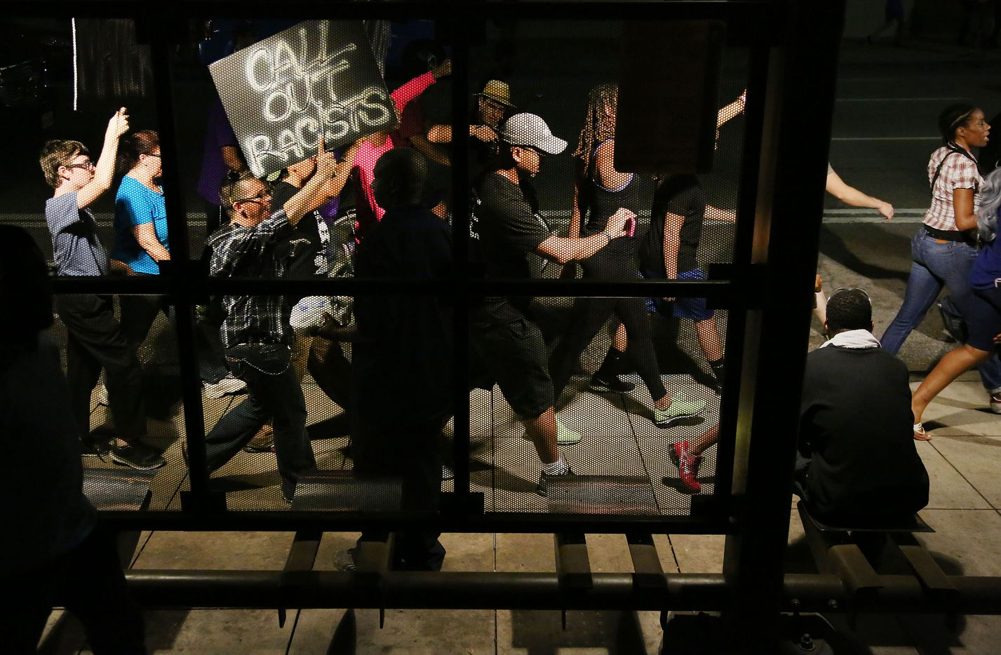 """Protesters pass a transit stop while marching during a protest held by the Next Generation Action Network in downtown Dallas Thursday September 22, 2016. The protest, which started at the Main Street Garden Park and is called """"Enough is Enough,"""" is in reaction to recent shooting by police in Tulsa and Charlotte. (Andy Jacobsohn/The Dallas Morning News)"""