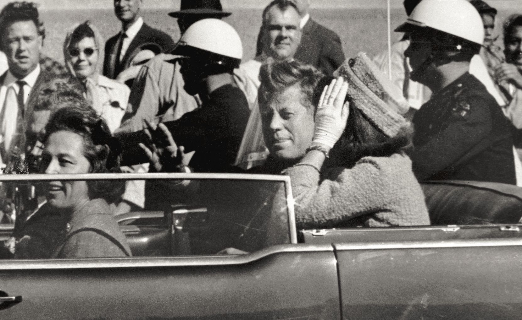 In this Nov. 22, 1963 file photo, President John F. Kennedy waves from his car in a motorcade approximately one minute before he was shot in Dallas. Riding with Kennedy are First Lady Jacqueline Kennedy, right, Nellie Connally, second from left, and her husband, Texas Gov. John Connally, far left. The National Archives has until Oct. 26, 2017, to disclose the remaining files related to Kennedy's assassination, unless President Donald Trump intervenes. (AP Photo/Jim Altgens, File)