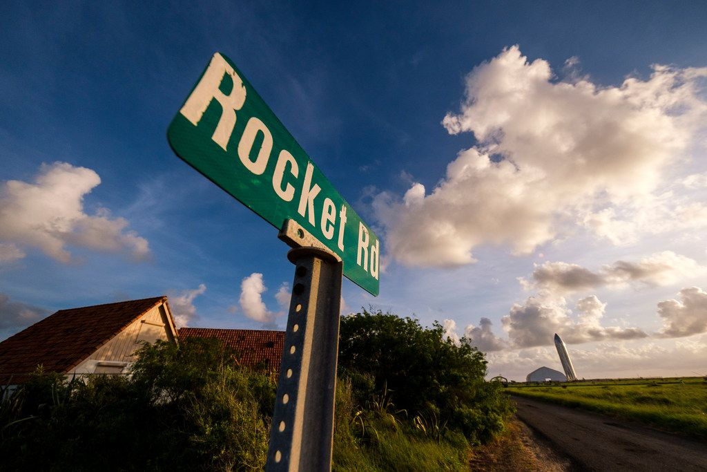 The sign for Rocket Road near is seen with a prototype of the SpaceX Starship spacecraft just after sunrise at the SpaceX Space Launch Facility in Boca Chica, Texas, on Sunday, Sept. 29, 2019.