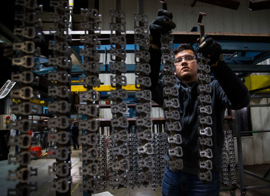 Jehu Salas hangs seatbelt parts that were manufactured inside the ITD Precision factory in Harlingen. J. Scott Hays, vice president of operations, moved the factory to Harlingen from the Houston headquarters in 1994 because of NAFTA.