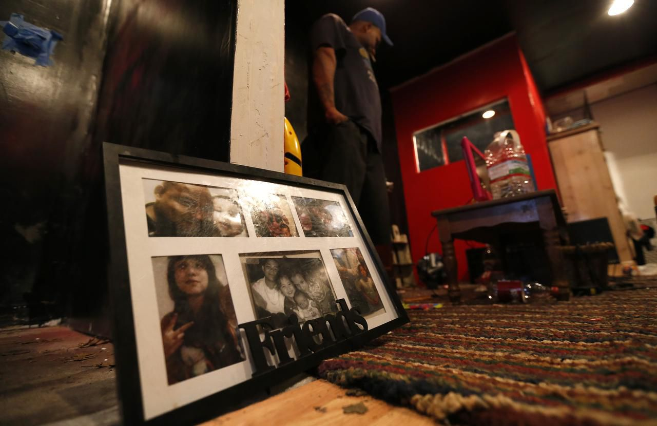 Jacob Ortega walks by family pictures placed on the floor inside a shed where his three children were found living without running water by a Child Protective Services worker in Dallas.