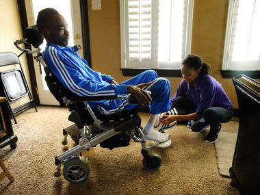 Dressed in one of his colorful Adidas track suits,  former NFL player Rickey Dixon   gets ready for the day with the assistance of his daily care giver Shanika Glover at his Red Oak, Texas home, Friday, April 7, 2017. (Tom Fox/The Dallas Morning News)