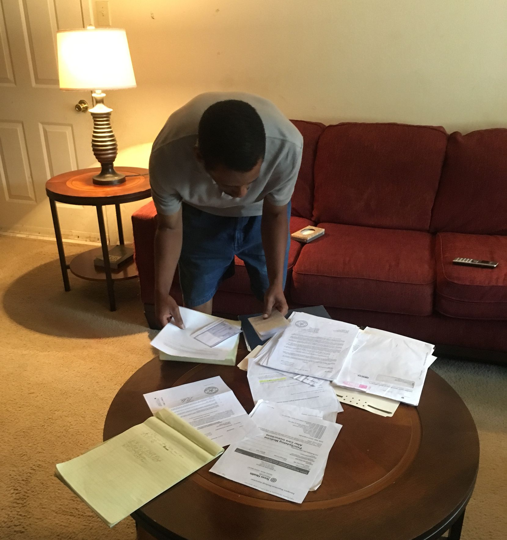 Fred Rooters sorts through paperwork in his mother's living room as he tries to figure out her legal case.