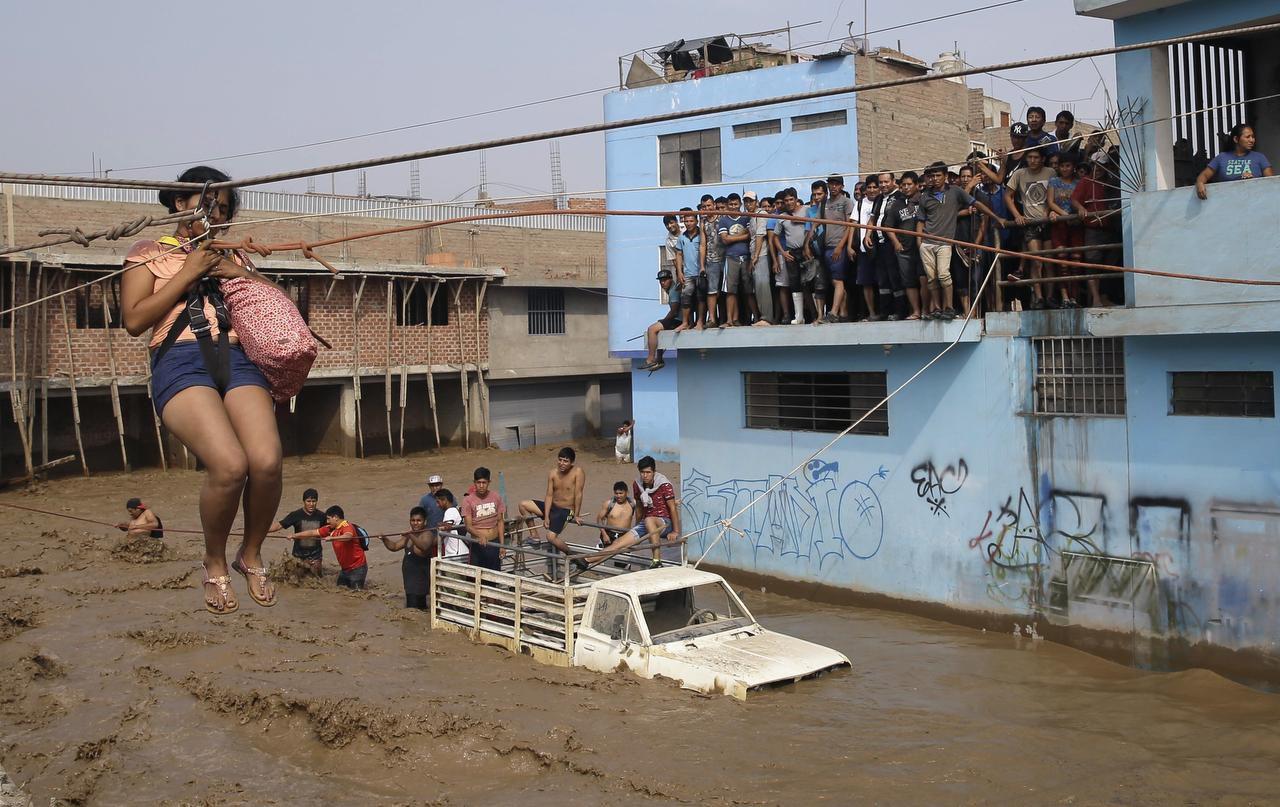 Una mujer es jalada hacia un lugar seguro mediante una cuerda en Lima, Perú. Las lluvias y deslaves han provocado muertes y caos en la capital donde suele llover poco. (AP/MARTIN MEJÍA)
