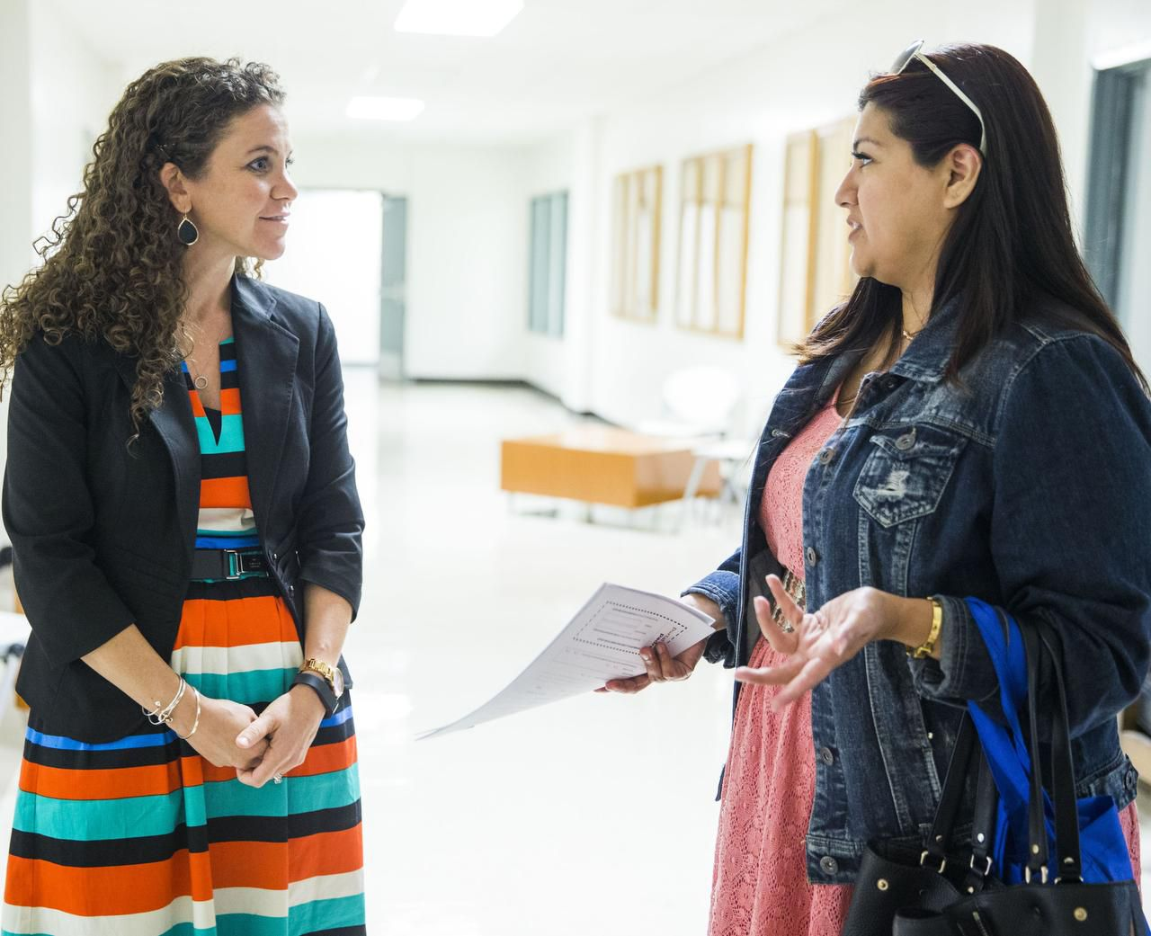 Principal Sarah Ritsema, left, helps Calette Benavidez with paperwork for her daughters during a community barbecue for Innovation, Design and Entrepreneurship Academy at Fannin High School in Dallas.