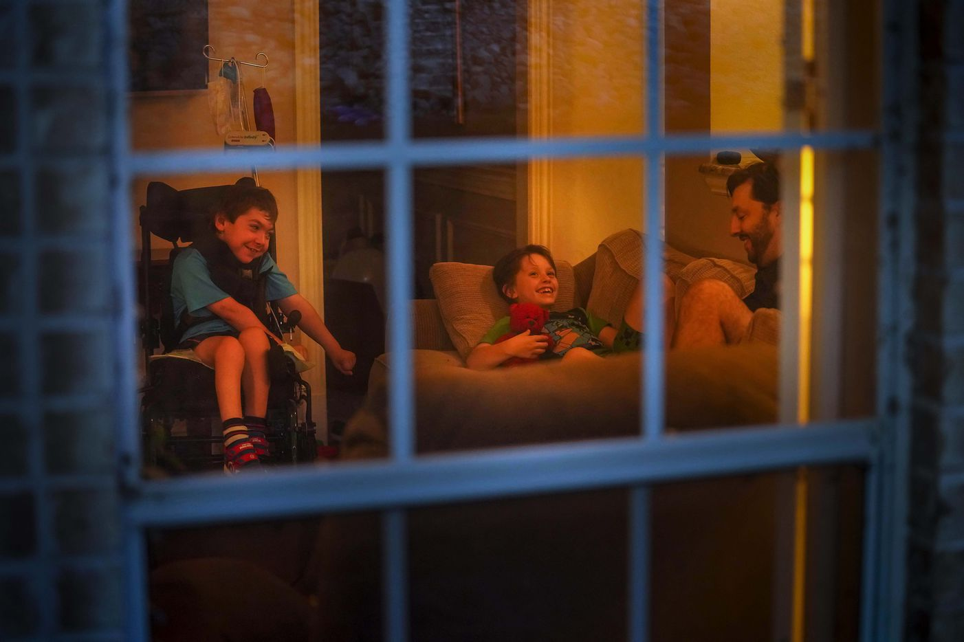 Jeff Carlton reads to his sons Jeffrey, 9, and Scotty, 11, in their living room during the family's extended COVID-19 quarantine at their home on Thursday, July 30, 2020, in Arlington, Texas. After two the two boys tested positive for COVID-19, the family says they learned to separate while the stuck together. Since the start of the pandemic, the Carltons had taken every precaution to keep their family healthy. But when the virus invaded their home, infecting their boys, they say they were unprepared.
