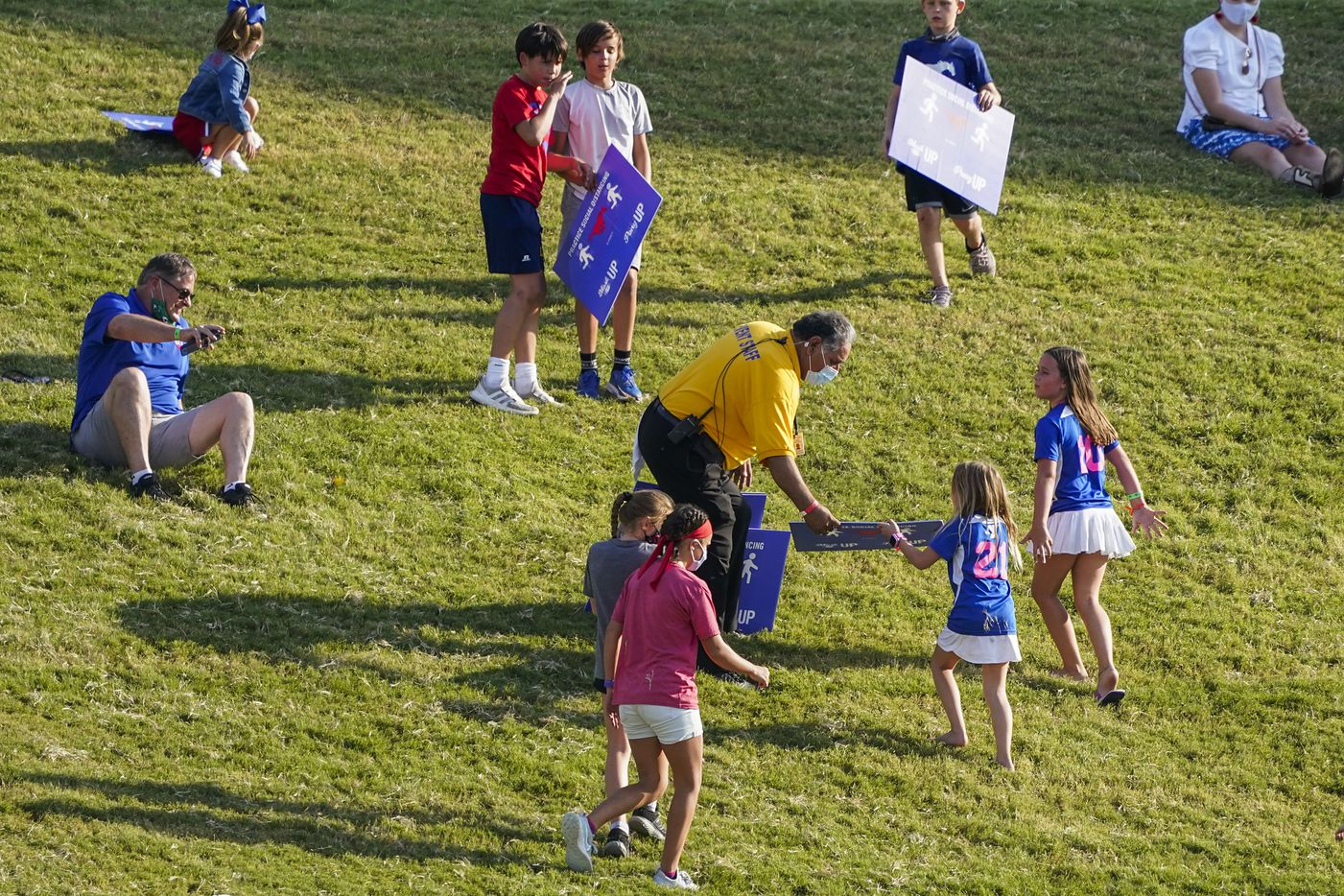 A stadium official collects social distancing signs from children who were using them to slide down the hill in the south end zone during the second half of an NCAA football game between SMU and Memphis at Ford Stadium on Saturday, Oct. 3, 2020, in Dallas.