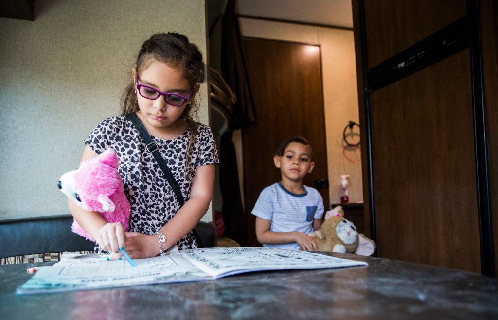 Trinity Vega, 7, and Sebastian Vega, 5, play inside a trailer, which is parked in the driveway of their home on Kelso Lane in Garland, Texas. The Vegas have been living in a trailer since March, while they wait for a ruling from an insurance mediator.