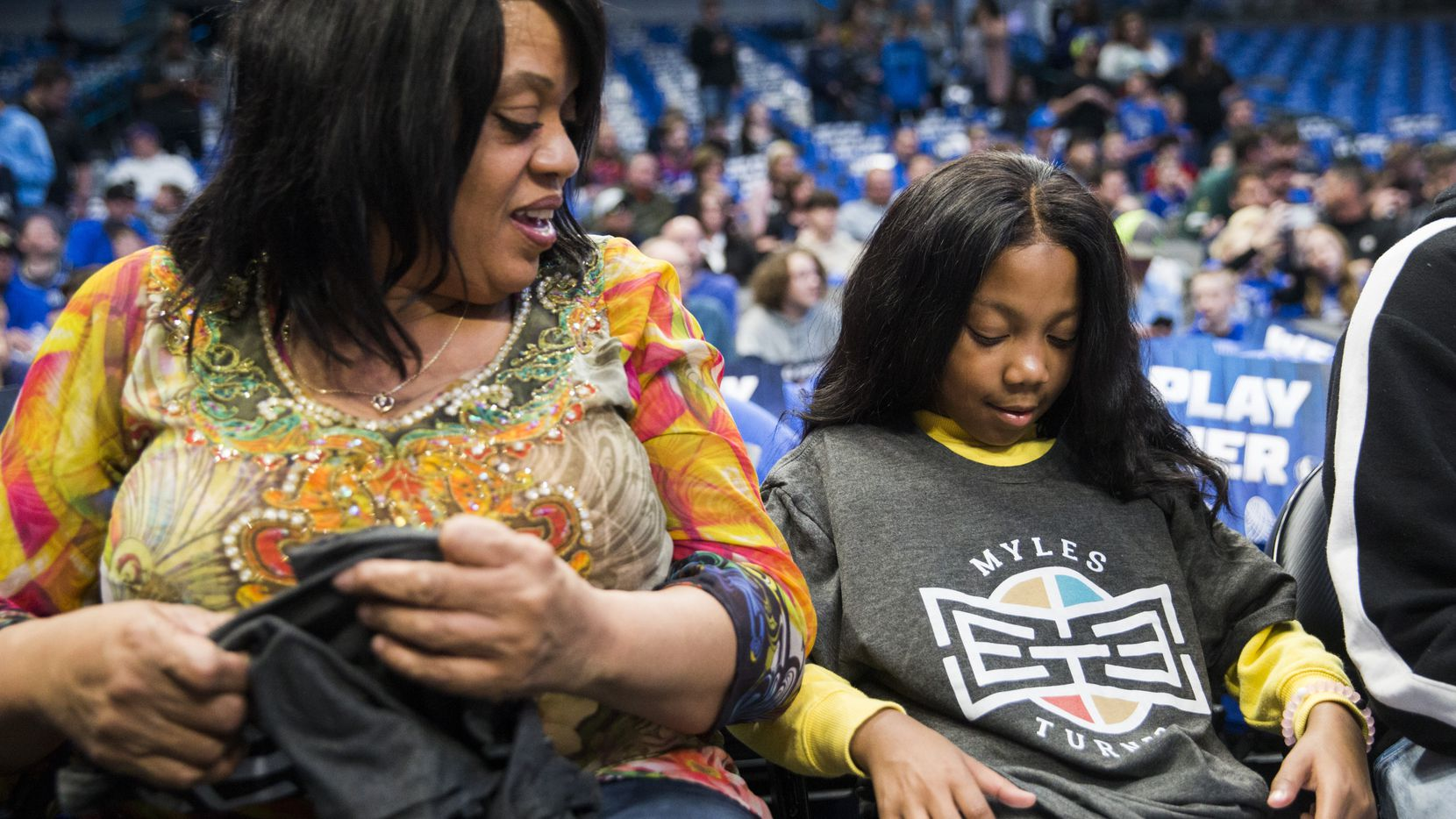 A'Myah Moon, 11, puts on a T-shirt with Indiana Pacers center Myles Turner's No 33 as her grandmother, Sheila Walker, watches her before an NBA game between the Indiana Pacers and the Dallas Mavericks on Sunday, March 8, 2020, at American Airlines Center in Dallas. Moon, who has a rare disease, was bullied at school. Turner and his family reached out to meet with Moon before the game.