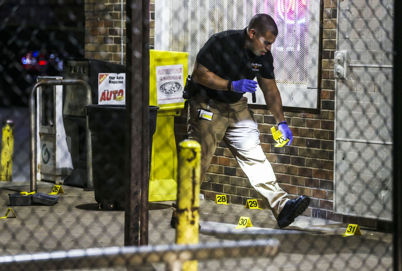 Fort Worth police officers investigate the scene of a shooting at Smokey's Paradise Food Mart in Fort Worth on Sunday.