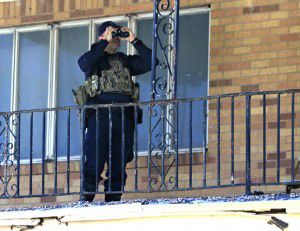 A police officer uses binoculars across from the Muhammad Mosque to monitor the situation. (Jae S. Lee/Staff Photographer)