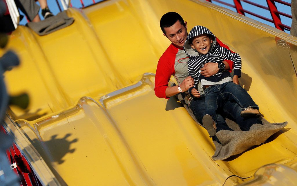 "Jaime Flores and his son Jamie Flores Jr., 3, slide down the ""Super Slide"" during the Main Street Festival in downtown Grand Prairie in 2018."