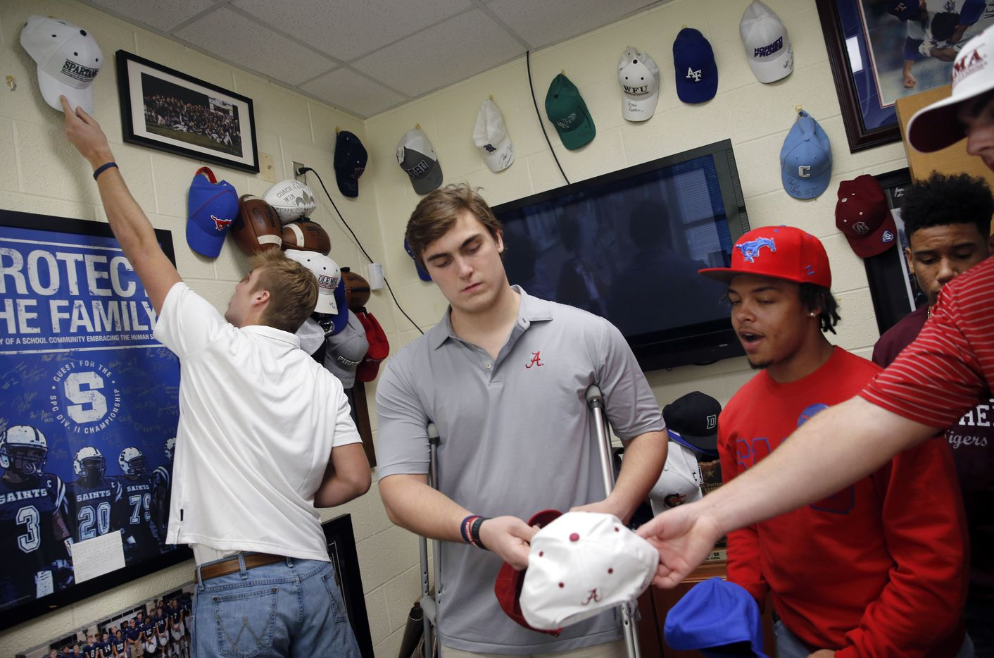 As part of tradition, players hang their signed hats in Athletics Director/Head Football Coach Aaron Beck's office at Fort Worth All Saints' Episcopal School. Paul Breedlove (Air Force) hangs hat (left) as Tommy Brockermeyer (Alabama, center) and Montaye Dawson (SMU) wait their turn after everyone signed their national letters of intent, Wednesday, December 16, 2020. (Tom Fox/The Dallas Morning News)