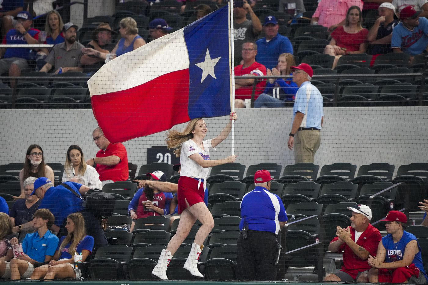 A member of the Texas Rangers Six Shooters squad runs a flag across the dugout before a game against the Minnesota Twins at Globe Life Field on Friday, June 18, 2021.