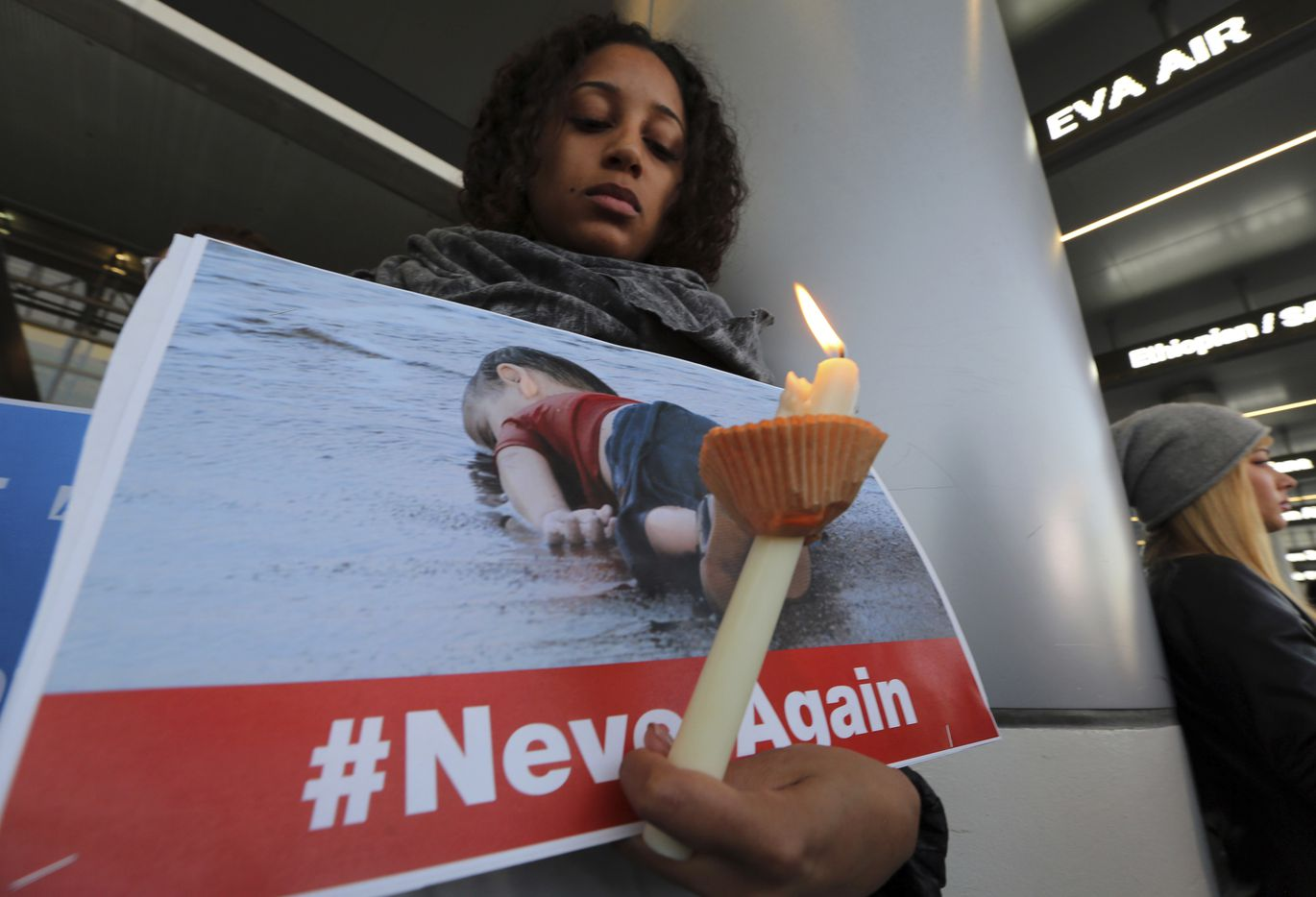 Avriel Epps of Los Angeles joins holds a well known photo of a refugee child who drowned as he was fleeing a war torn country, as hundreds of demonstrators opposed to President Donald Trump's executive order barring entry to the U.S. of seven predominantly Muslim countries at the Tom Bradley International Terminal at Los Angeles International Airport Saturday, Jan. 28, 2017.