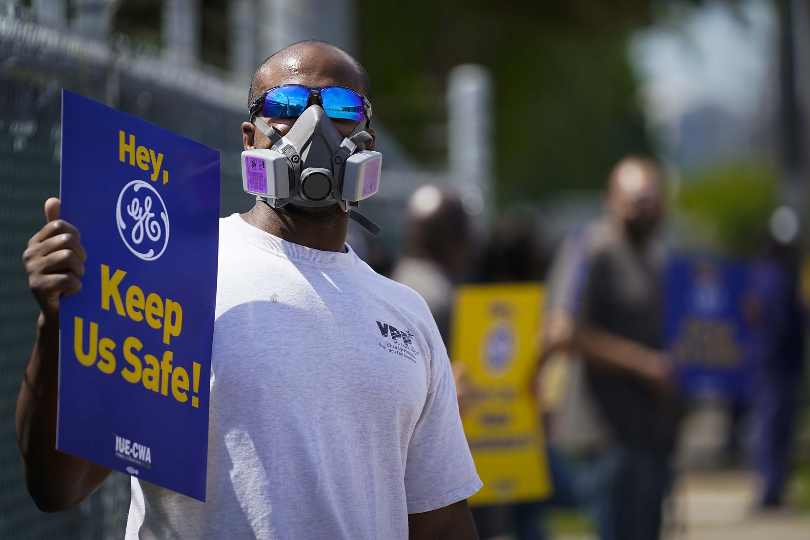 Cornelius Hunt wears a mask and holds a sign as he protests with fellow Iworkers outside GE Energy near Love Field.