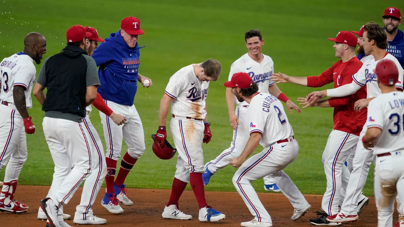 Texas Rangers' Brock Holt, center left with head down, Charlie Culberson (2) and the rest of the team celebrate Holt's walk-off single in the 11th inning of a baseball game in Arlington, Texas, Wednesday, June 9, 2021.