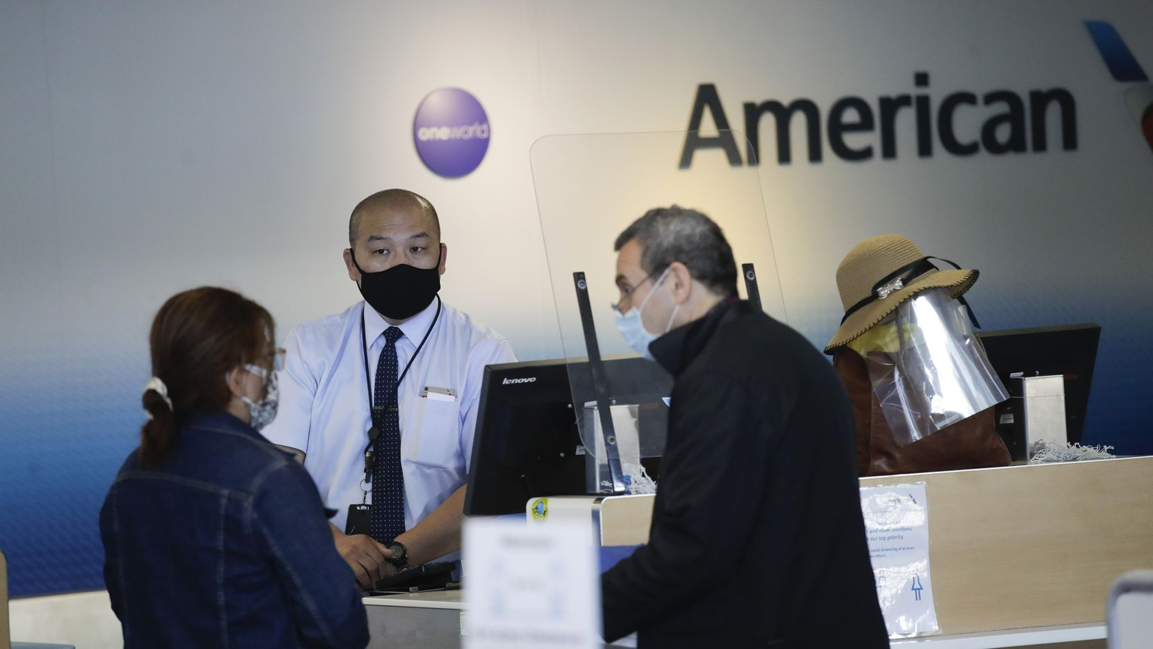 Travelers check in at the American Airlines terminal at the Los Angeles International Airport Thursday, May 28, 2020, in Los Angeles.