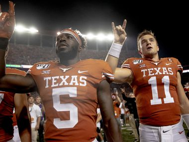 """FILE - Texas defensive back D'Shawn Jamison (5) and quarterback Sam Ehlinger (11) hold up the """"Hook 'em Horns"""" sign for the playing of """"The Eyes of Texas"""" following a win over Oklahoma State on Saturday, Sept. 21, 2019, in Austin."""