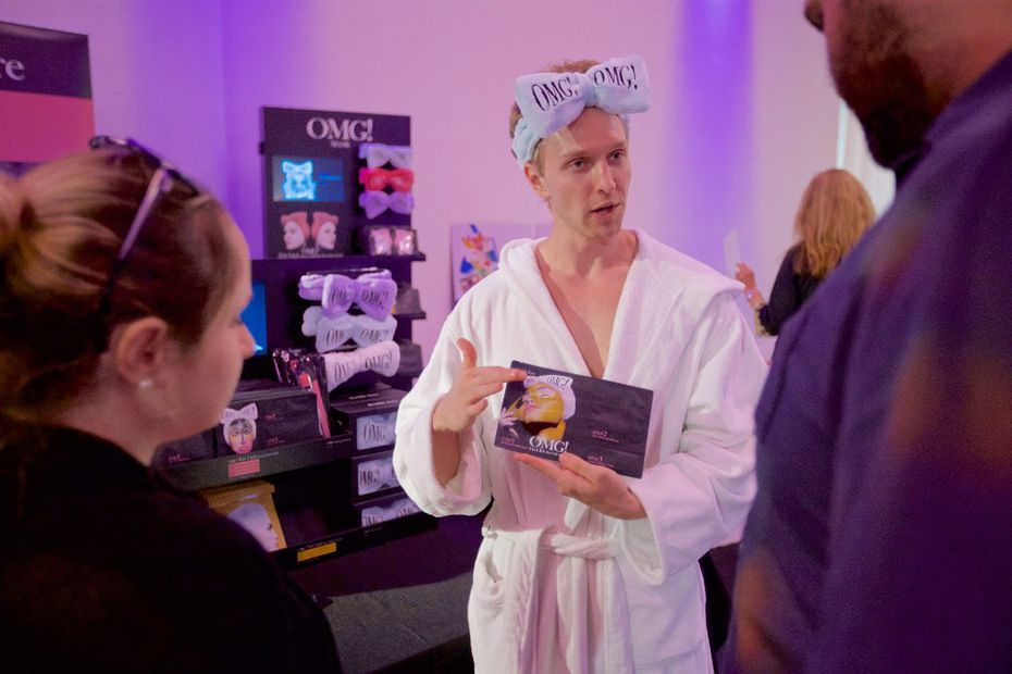 """Double Dare Spa Sales Rep Austin Brook, center, shows Viktoriya Erickson, left, and Andrew Erickson the """"OMG!"""" face mask product during the Indie Beauty Expo in Dallas."""