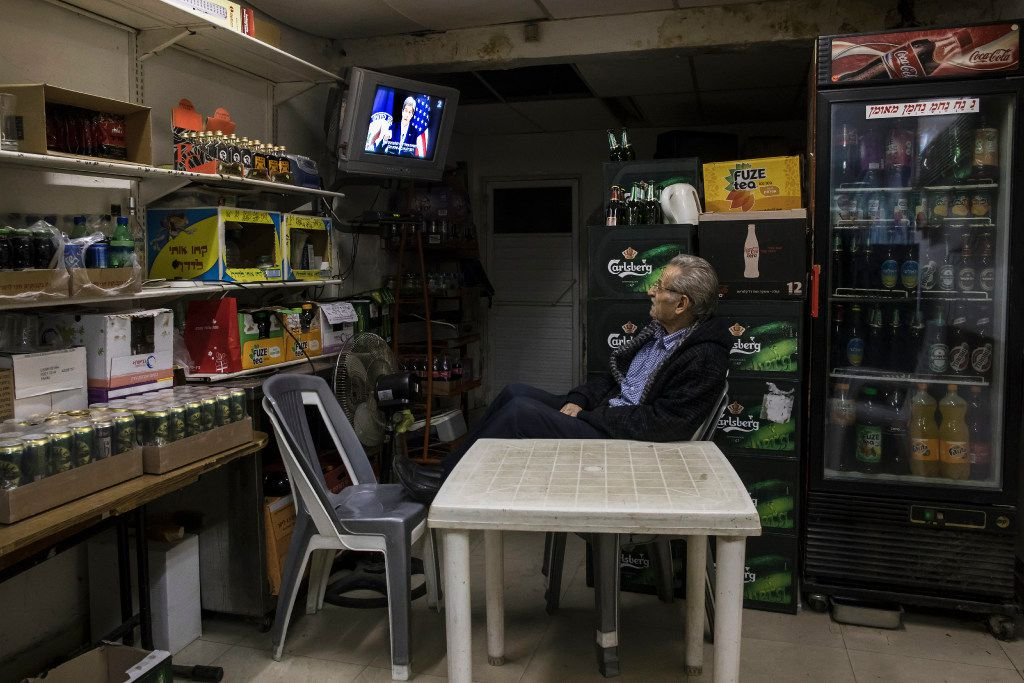 An Israeli grocery store owner watches  the US Secretary of State John Kerry speech at the State Department at Washington, in Sderot near the Israel and Gaza border, Wednesday, Dec. 28, 2016. I(AP Photo/Tsafrir Abayov)