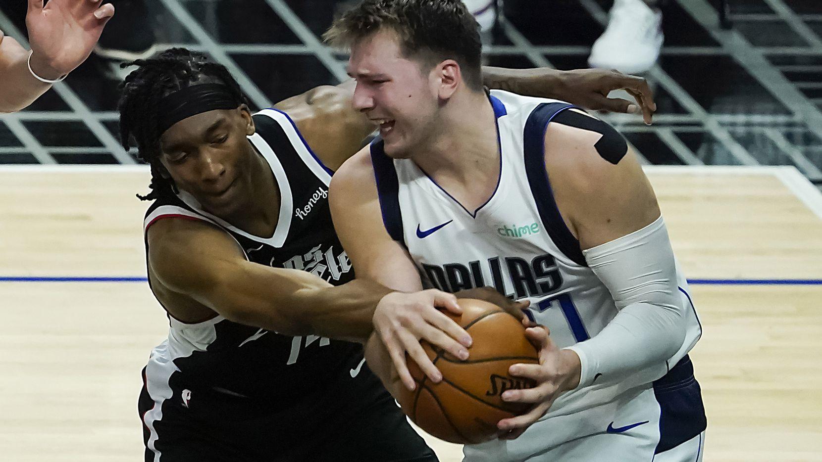 El guardia de los Mavericks de Dallas (der) protege el balón ante el acoso de Terance Mann, de los Clippers de Los Ángeles, el 2 de junio de 2021 en el Staples Center de Los Ángeles.