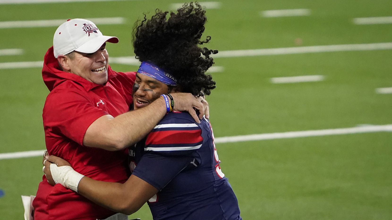 Denton Ryan offensive lineman Bryan Aguilar (56) hugs assistant coach Shane Tolleson as they celebrate a 59-14 victory over Cedar Park to win the Class 5A Division I state football championship game at AT&T Stadium on Friday, Jan. 15, 2021, in Arlington, Texas.