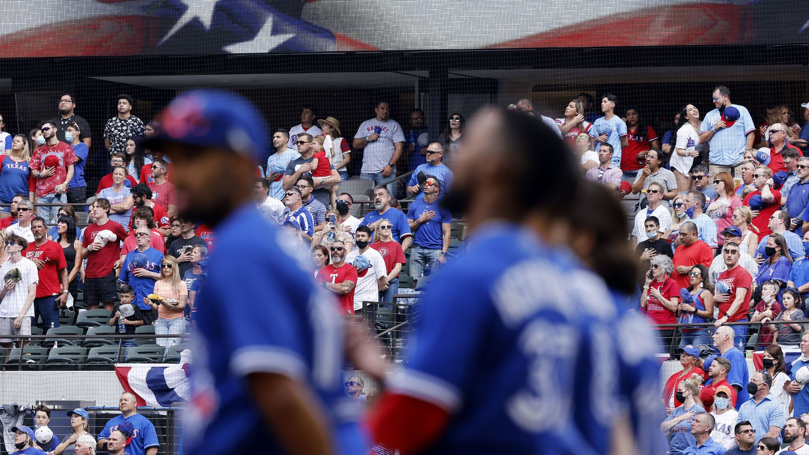 Texas Rangers fans stand and sing God Bless America in the eighth inning as the Toronto Blue Jays players watch at Globe Life Field in Arlington, Monday, April 5, 2021. The Texas Rangers were facing the Toronto Blue Jays in their home opener.