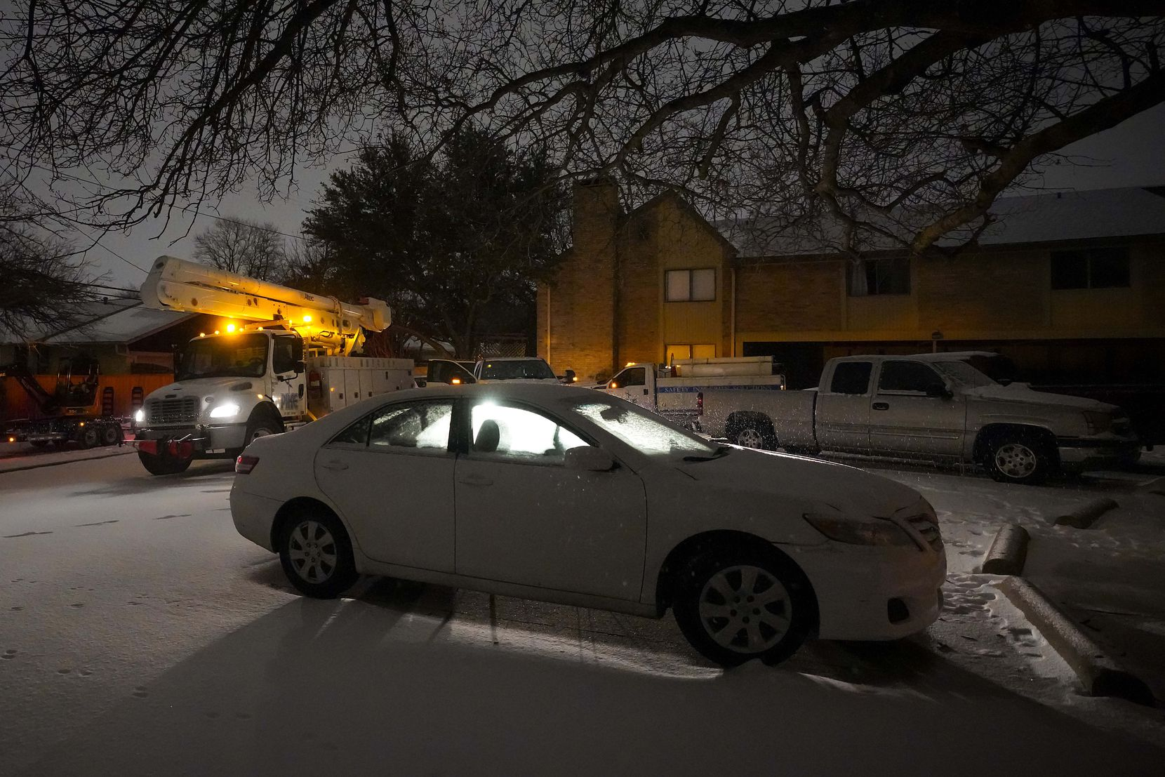 Power crews worked in a darkened Richardson apartment complex after a second winter storm brought more snow, continued freezing temperatures and continuing power outages to North Texas on Feb. 16, 2021.