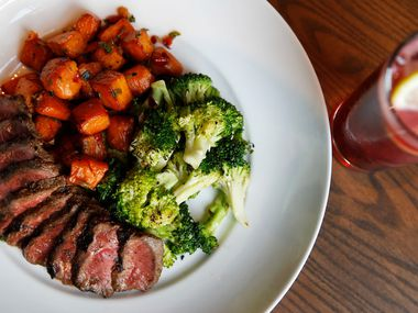 Steak bowl with sweet potato hash and broccoli with a blackberry buck cocktail at HG Sply Co. in Trophy Club, Texas on Thursday, August 15, 2019. (Vernon Bryant/The Dallas Morning News)