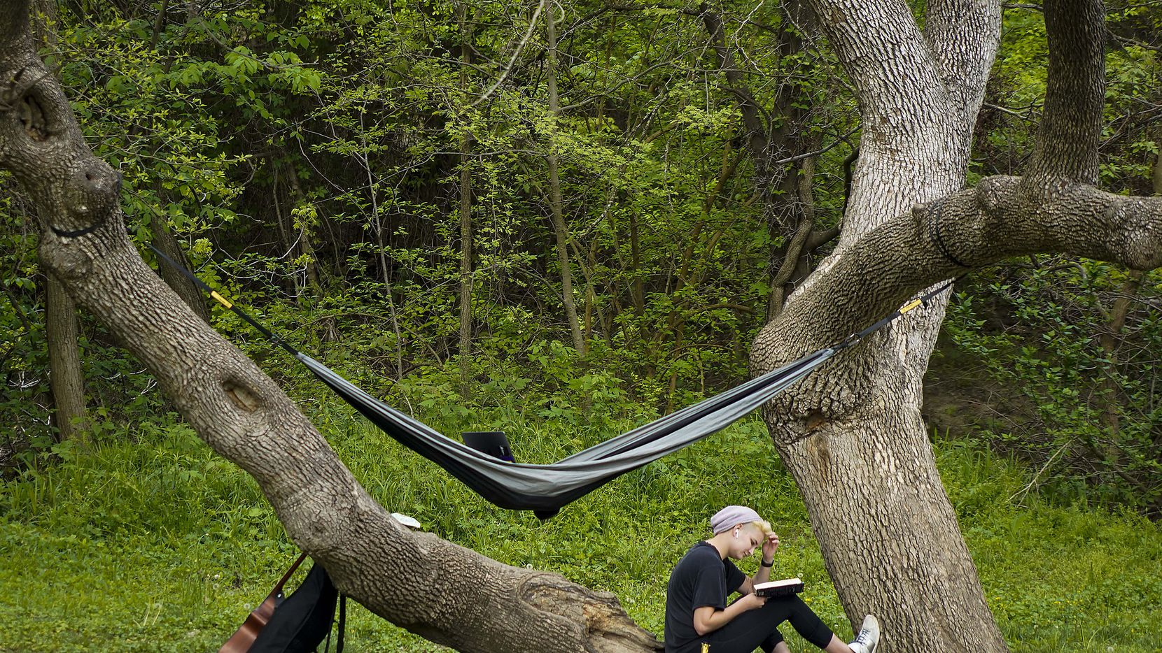 With a book, a hammock, a musical instrument, and a beverage, a woman enjoys time outdoors in Prairie Creek Park on Sunday, March 29, 2020, in Richardson, Texas.