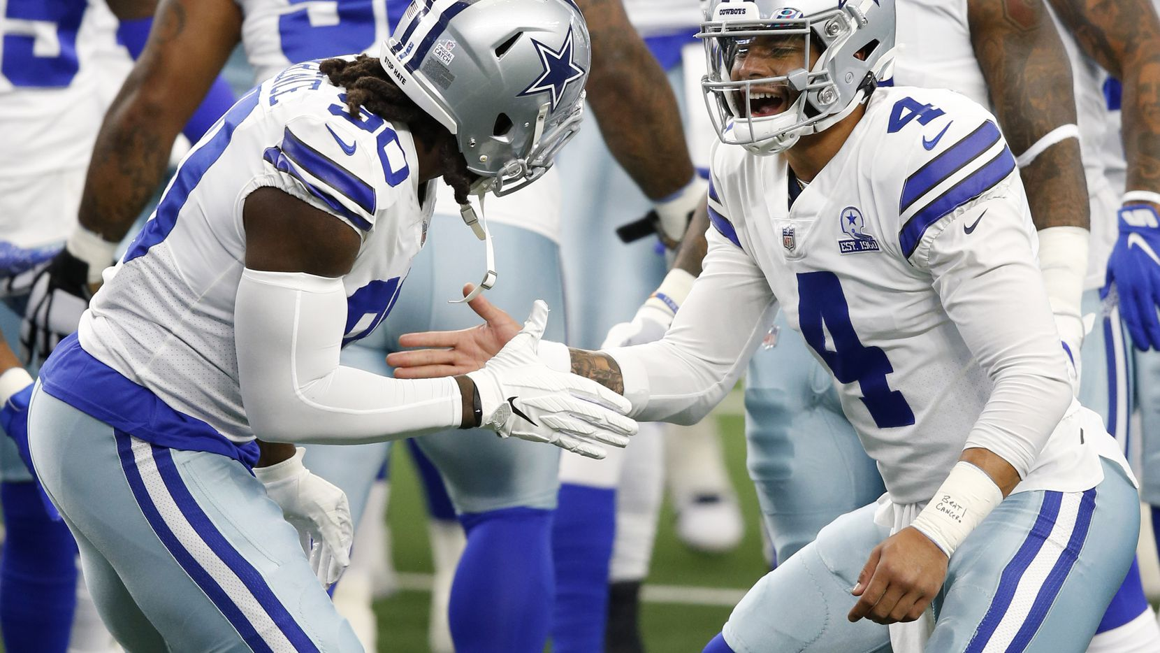 Cowboys quarterback Dak Prescott (4) greets defensive end DeMarcus Lawrence (90) during warmups before a game against the Browns on Sunday, Oct. 4, 2020, at AT&T Stadium in Arlington.