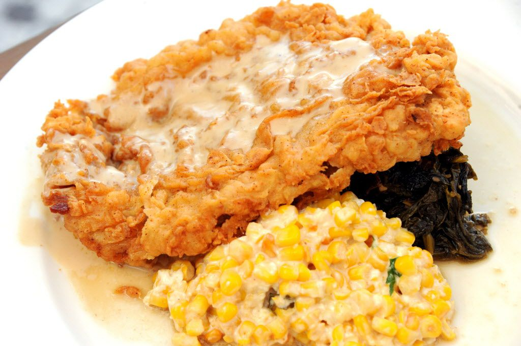 """The chicken fried ribeye sits atop """"naughty"""" creamed corn, beer braised mustard greens and a bacon redeye gravy at Pink Magnolia."""