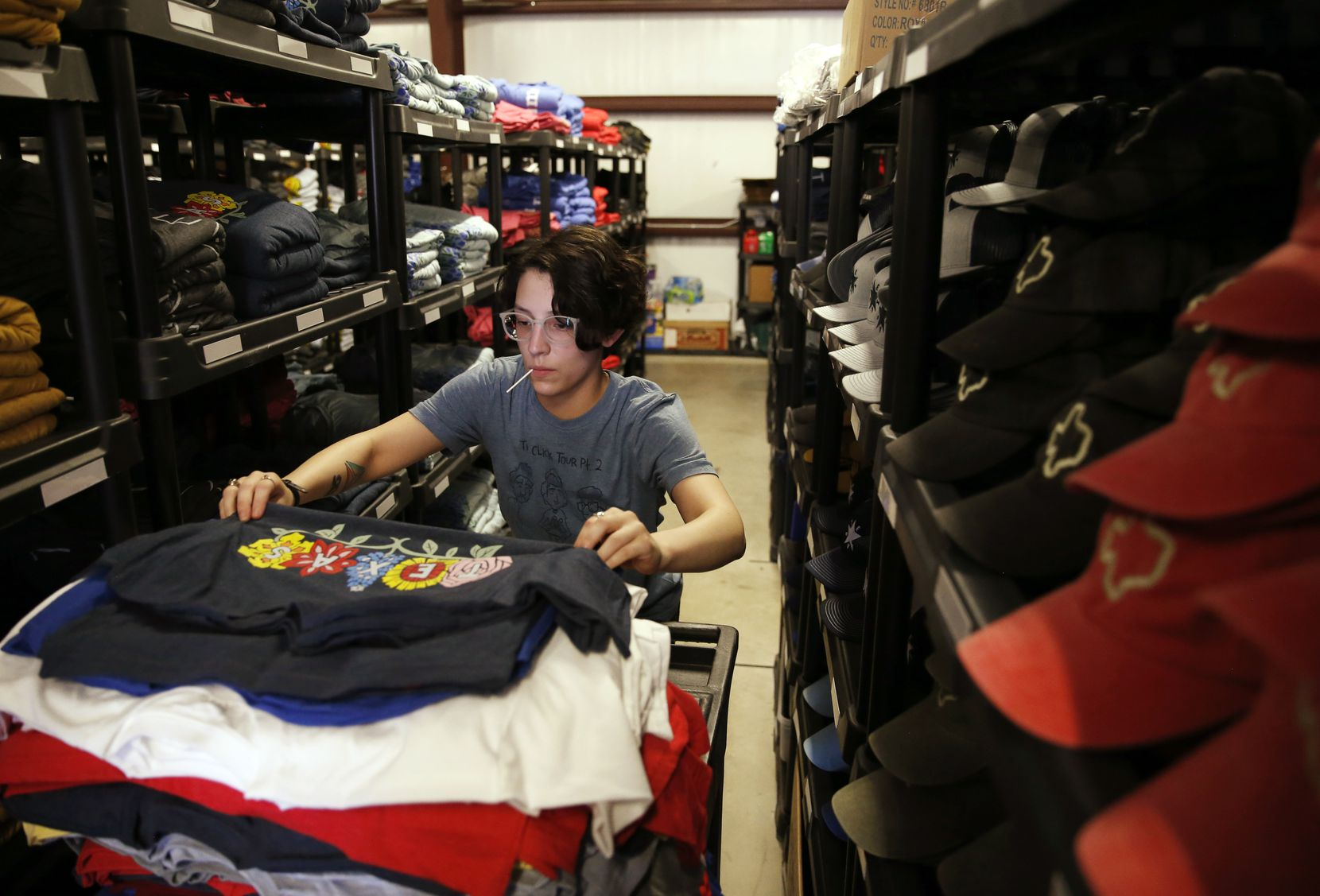 Nina Burton works on filling an order as she makes her way through aisles of merchandise from Tumbleweed TexStyles at Printed Threads warehouse in Keller.