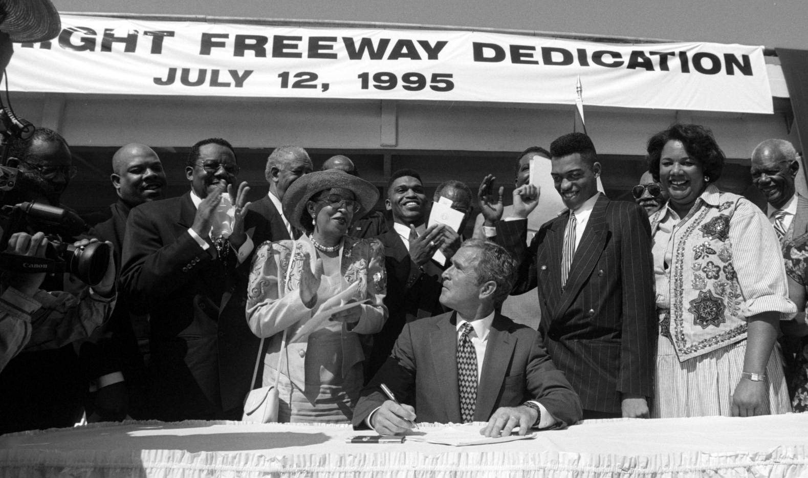 Gov. George W. Bush finishes the ceremonial bill signing during the official dedication of the new S. M. Wright Freeway in honor of the late Rev. Dr. Sylvester M. Wright of the People's Missionary Baptist Church in Dallas in 1995. The section of freeway is located on U.S. Highway 175 just south of downtown Dallas.