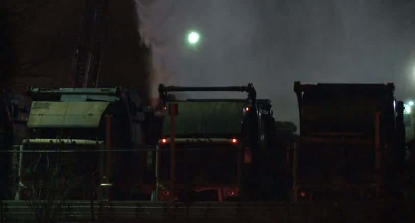 Garbage trucks are doused with water after fire and explosions broke out Tuesday at a waste collection facility in Haltom City.