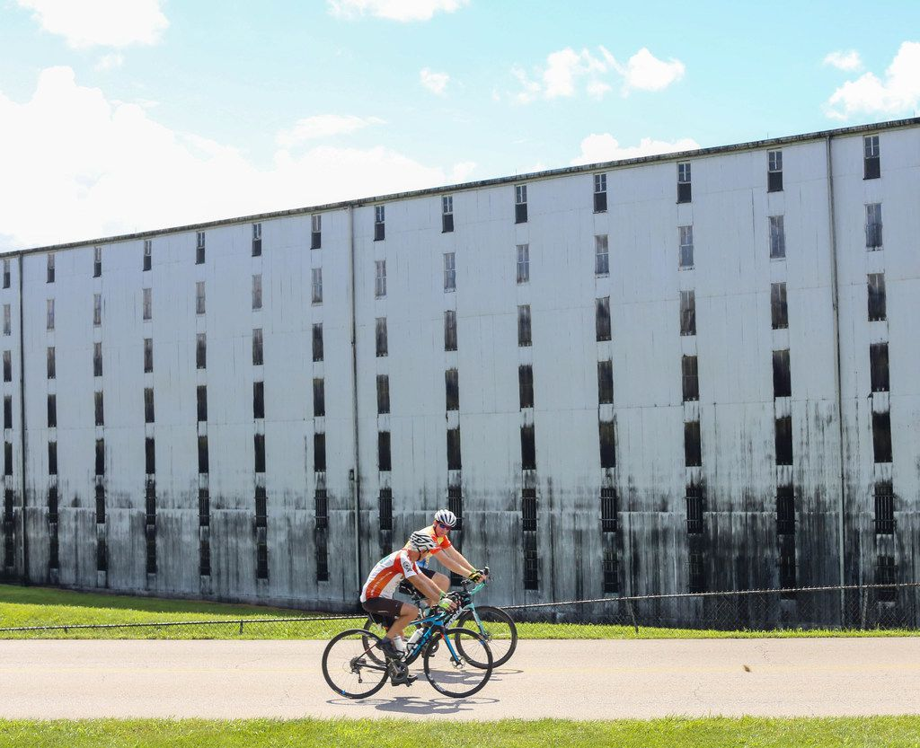 Cyclists ride past a rickhouse -- a building where bourbon barrels age — at Heaven Hill Distillery in Bardstown, Ky.